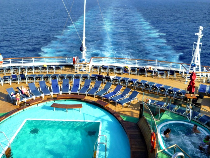Aft pool and hot tub overlooks a cruise ship's wake on the blue ocean