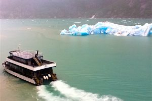 A small excursion boat safely navigate in an Alaskan fjord to get a closer look at icebergs