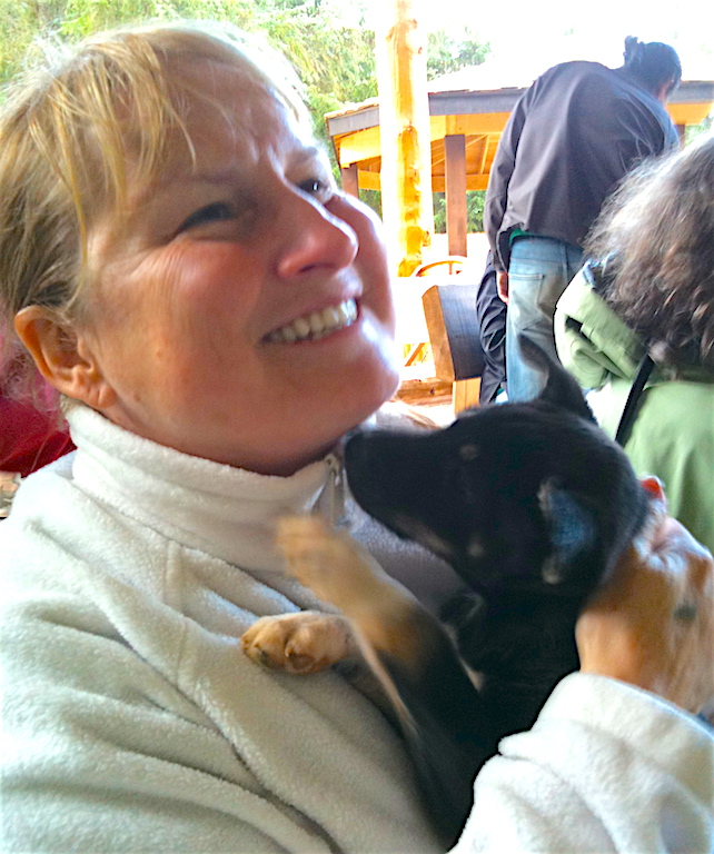 Elaine snuggles with an Alaskan husky puppy near Skagway, Alaska