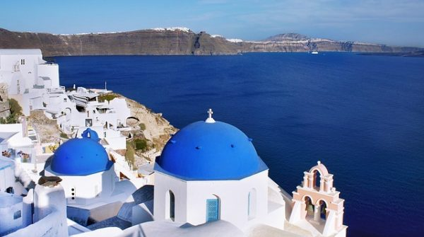 Blue domed Santorini church overlooking ocean below